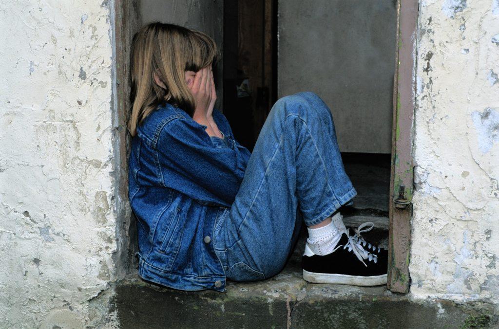 fille qui pleure dans le cadre d'une porte, jeans et veste en jeans