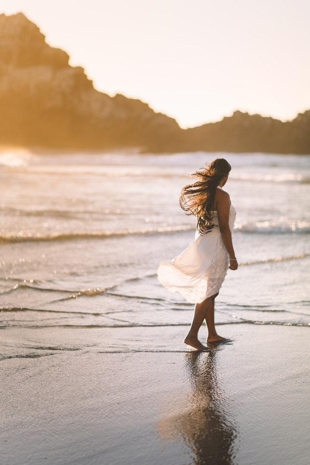 femme sur la plage avec robe blanche au vent