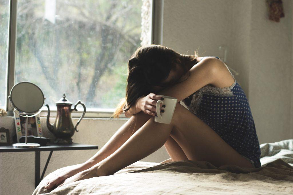 Pleurer, femme, sur un lit, fenêtre et tasse de café