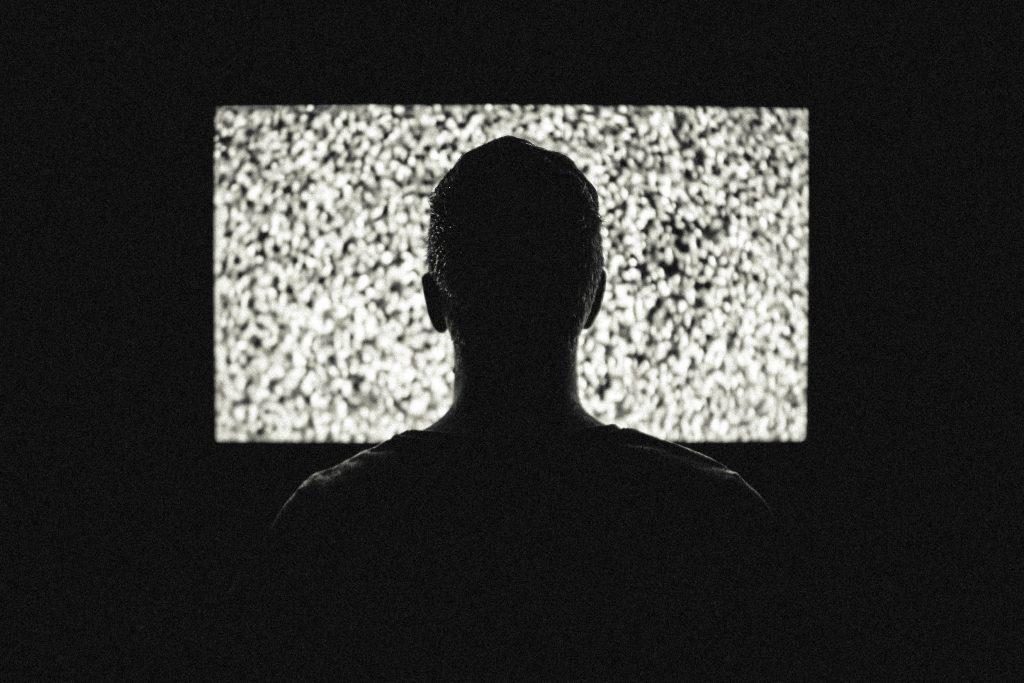 homme devant la télé qui «griche», noir et blanc