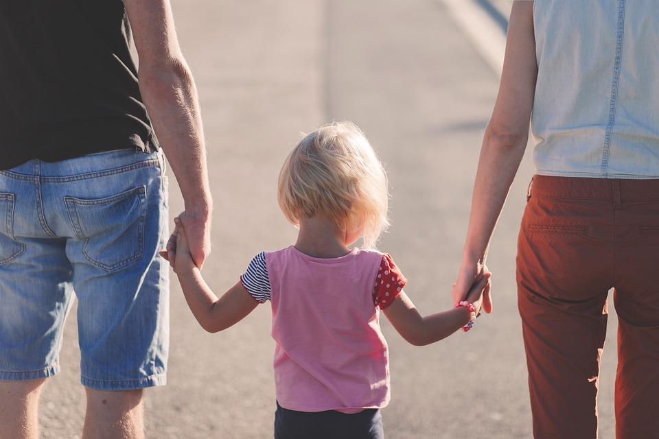 enfant blond tenir les mains parents