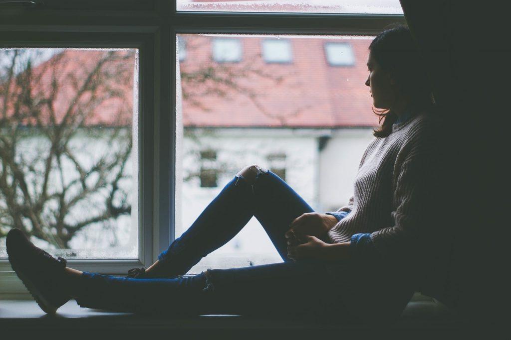 femme assise contre fenêtre