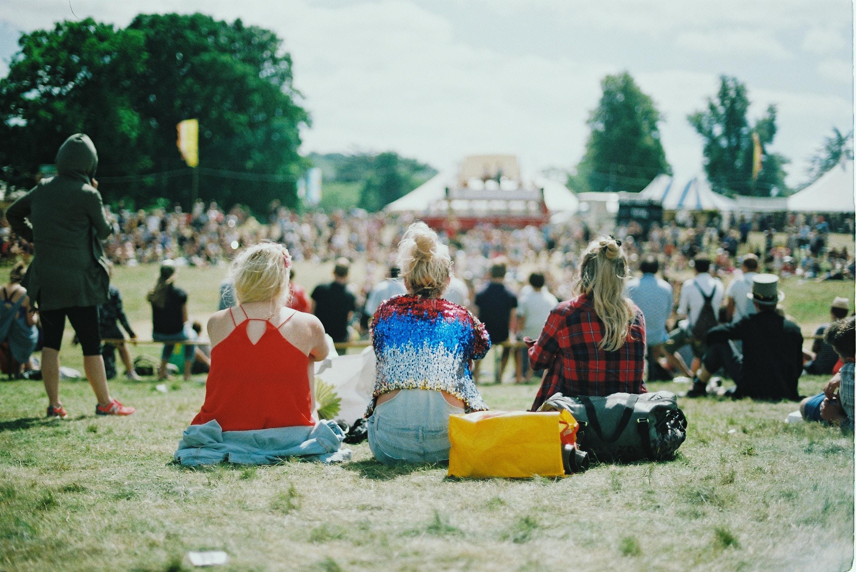 trois filles assises dans un festival
