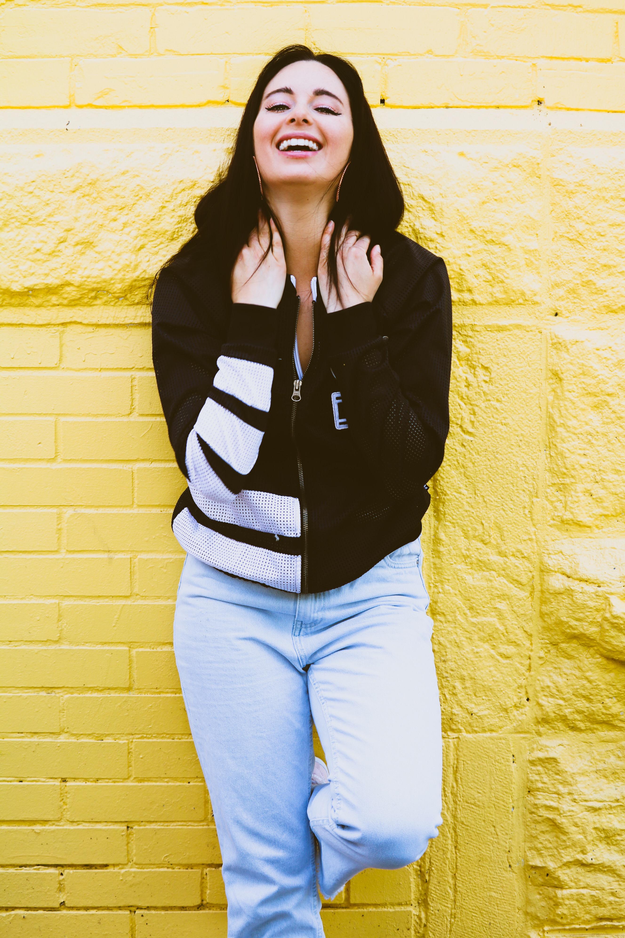 Femme qui rit devant un mur jaune