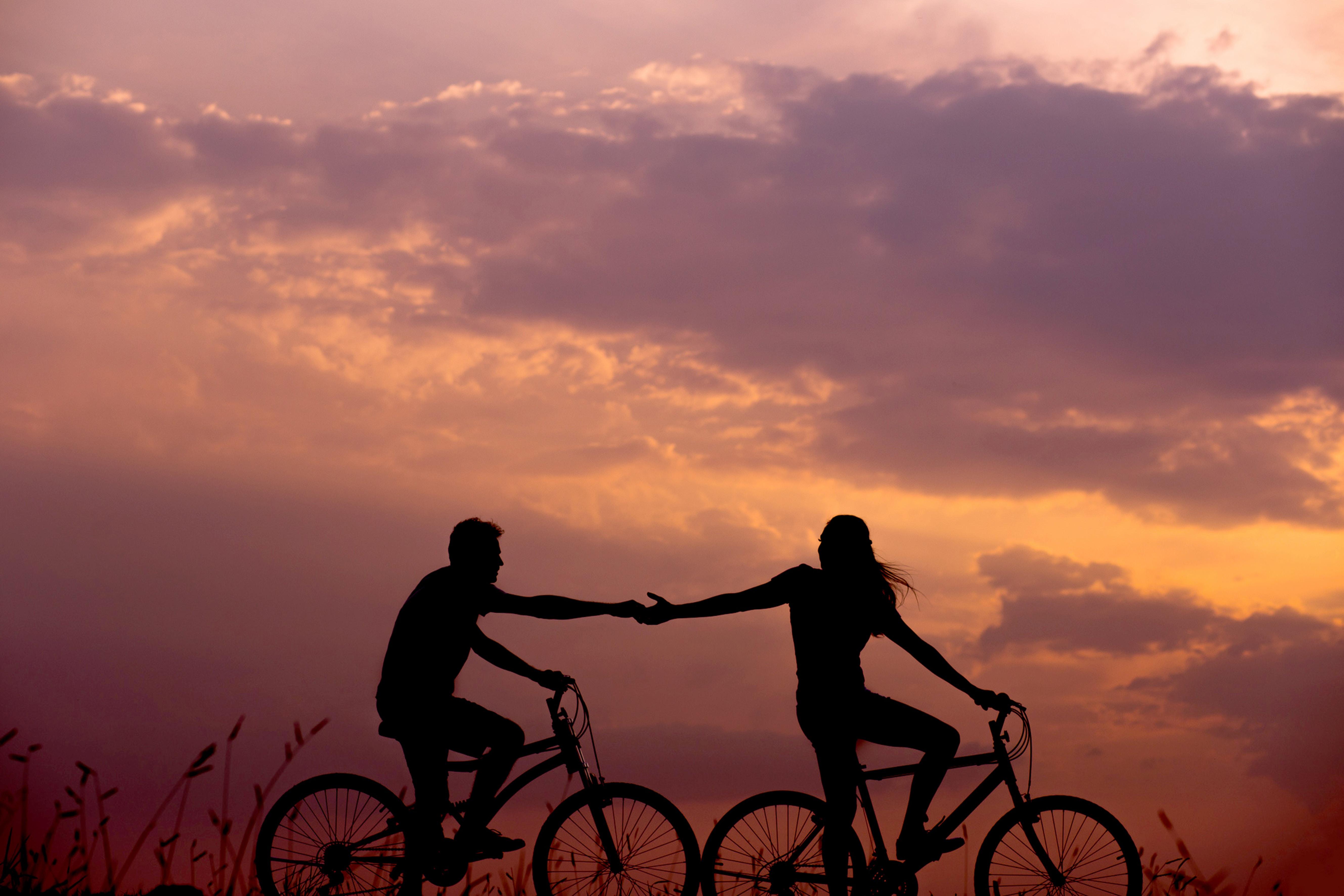 couple tenir la main vélos coucher de soleil