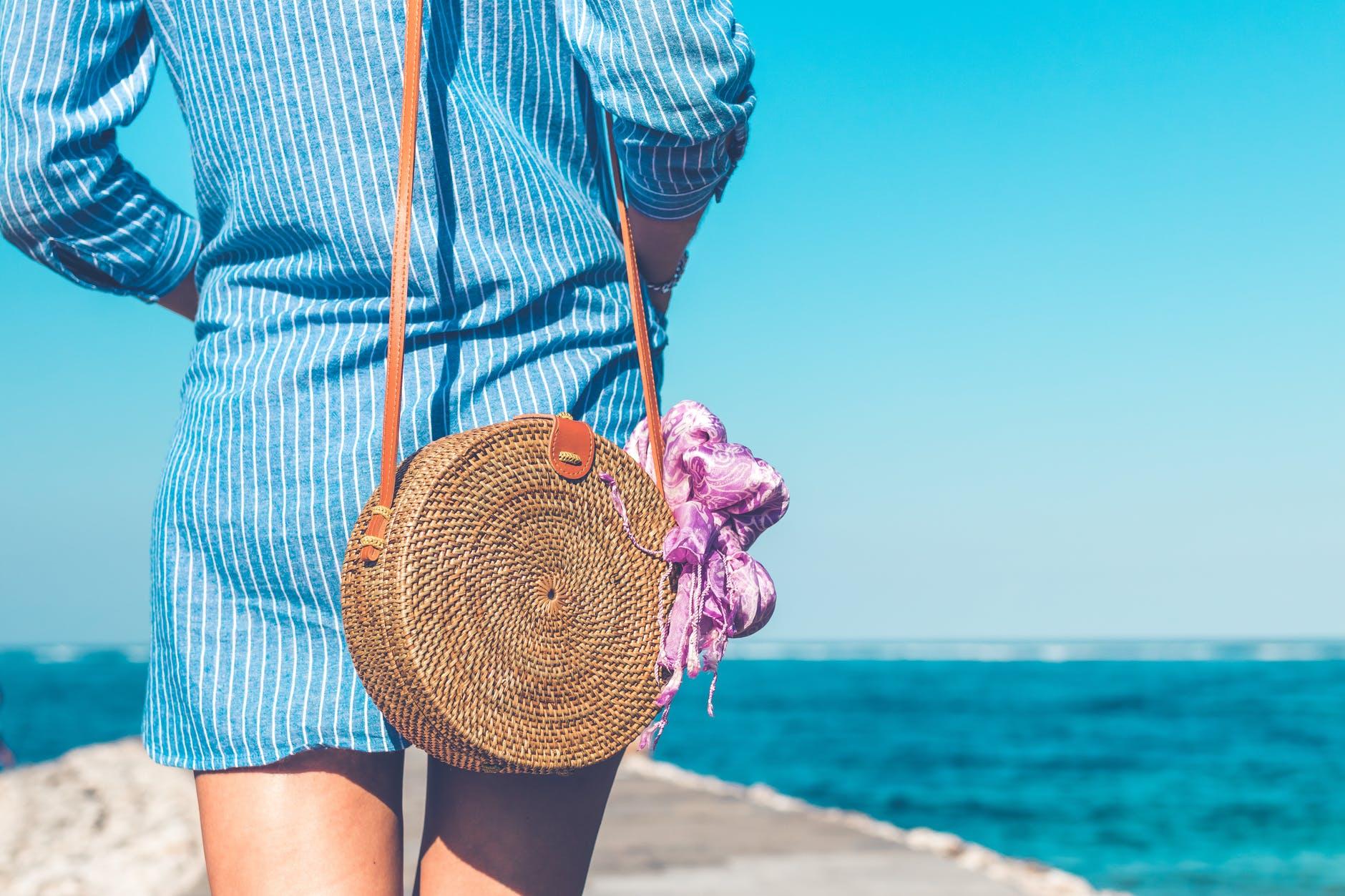 femme de dos avec sac en osier et robe en jeans