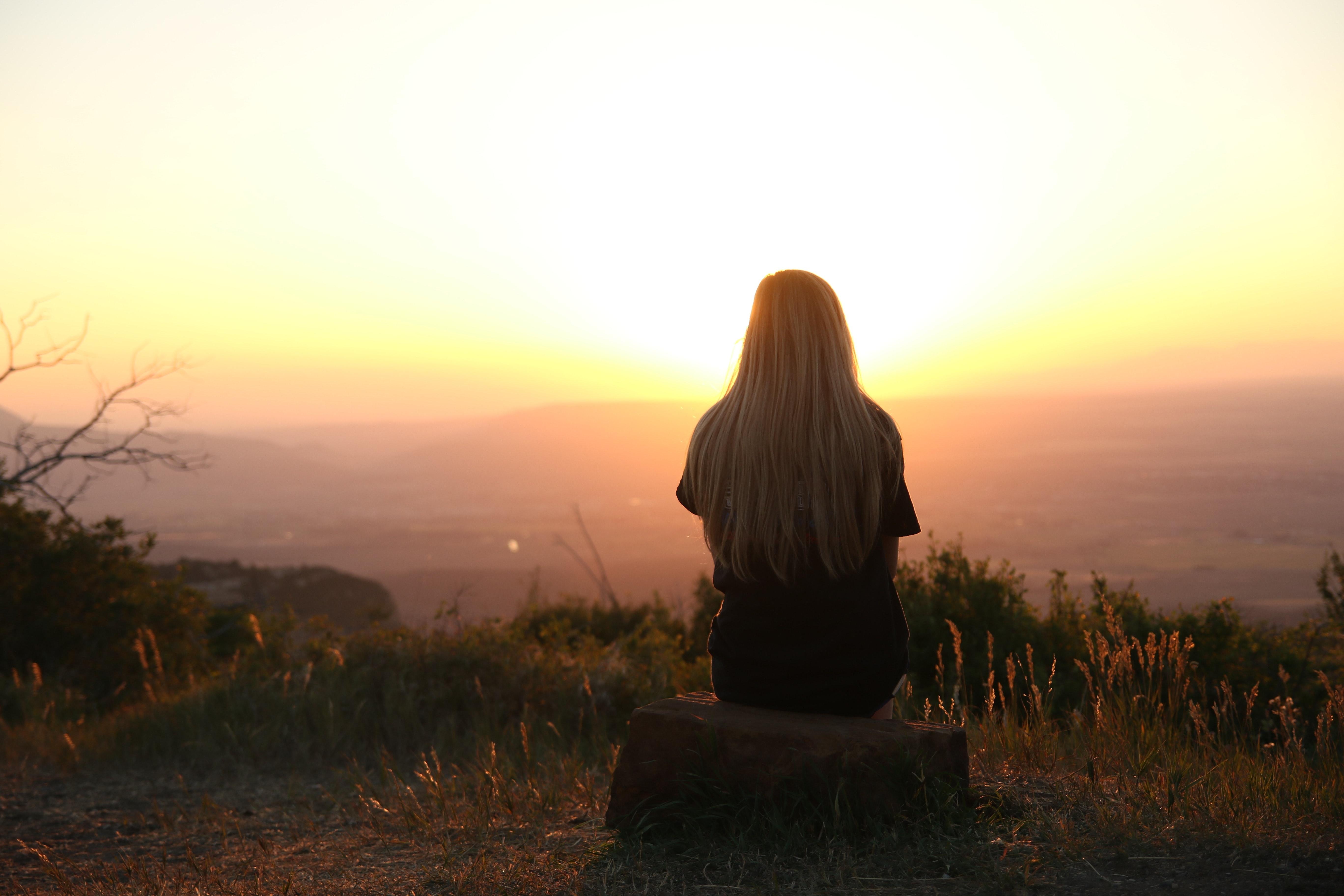 fiille de dos assise coucher de soleil célibataire