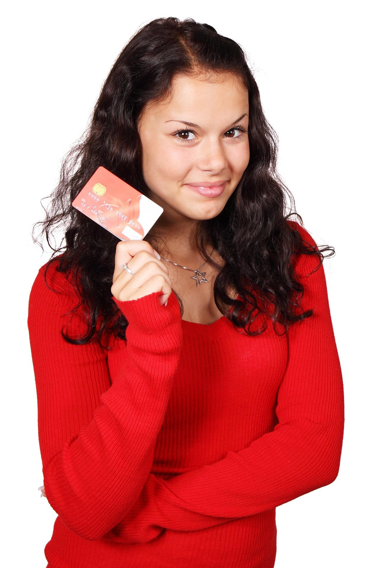 une fille qui tient une carte de crédit