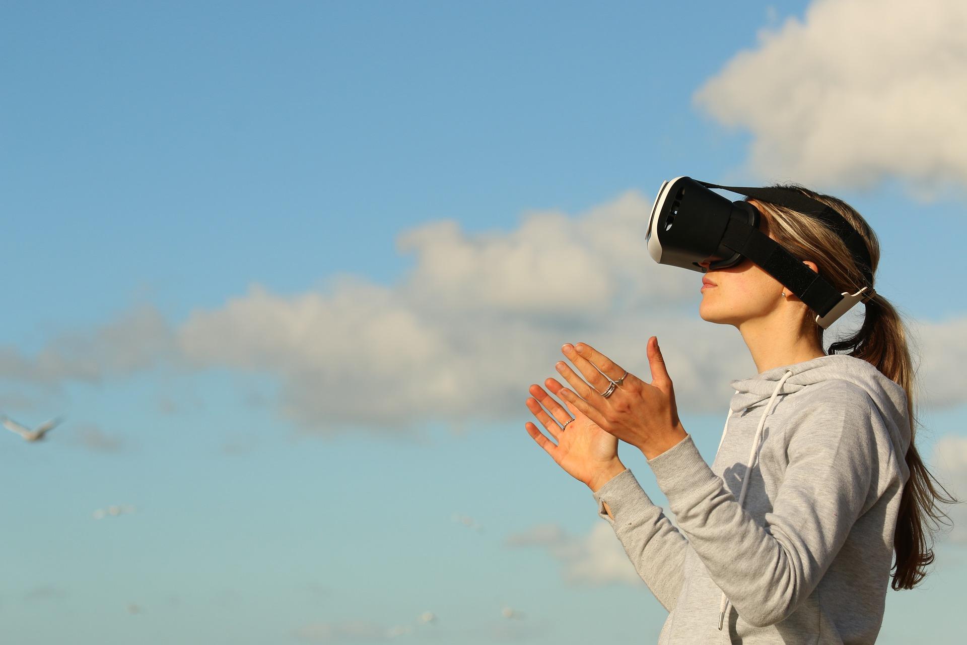 une fille qui porte un casque de réalité virtuelle et derrière elle on peut voir le ciel
