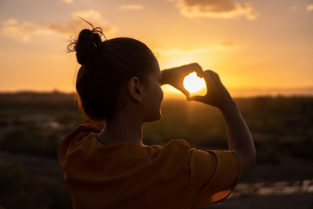 femme mains coeur coucher de soleil