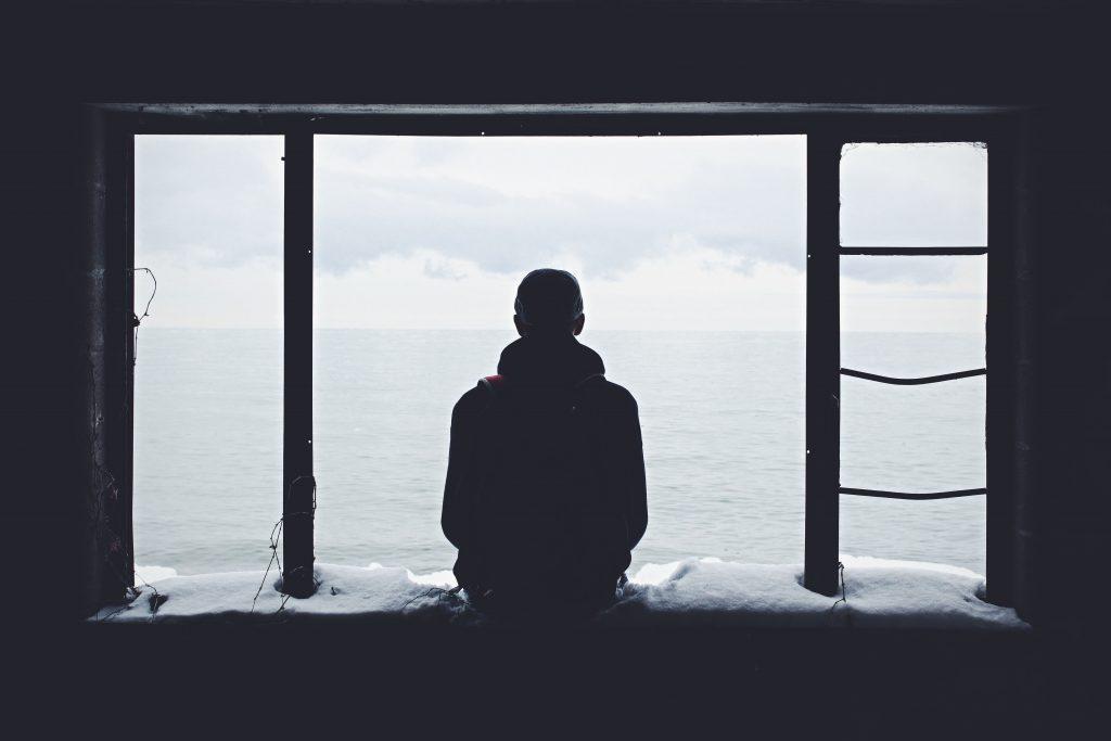 homme assis dans une fenêtre devant l'eau