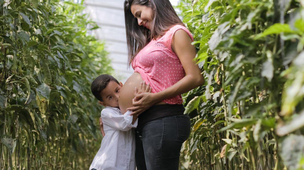 petit garçon qui embrasse le ventre de sa maman enceinte