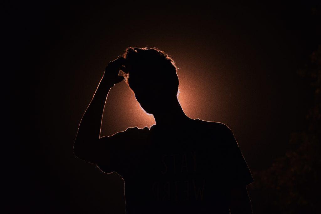 silhouette d'un homme éclairé de derrière