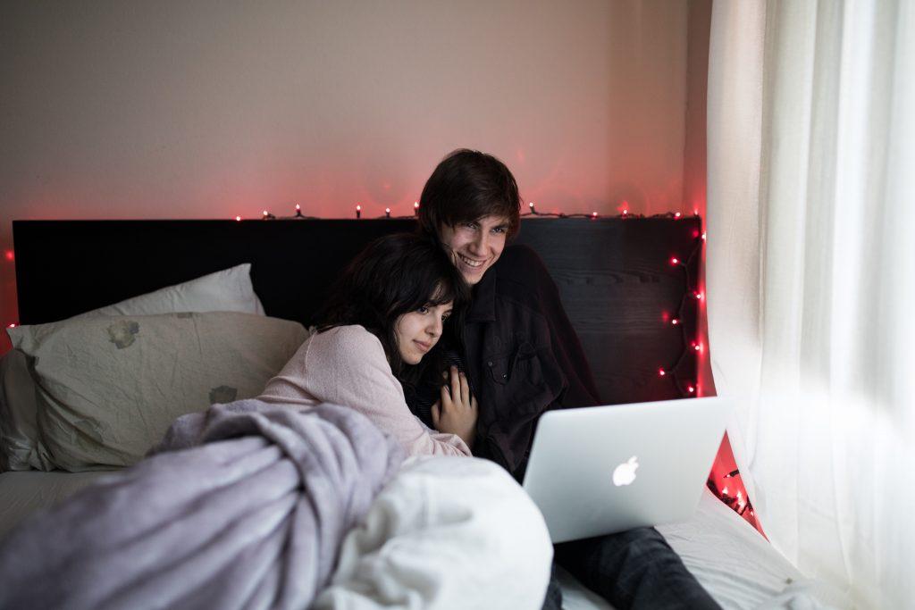 couple qui écoute l'ordinateur dans un lit