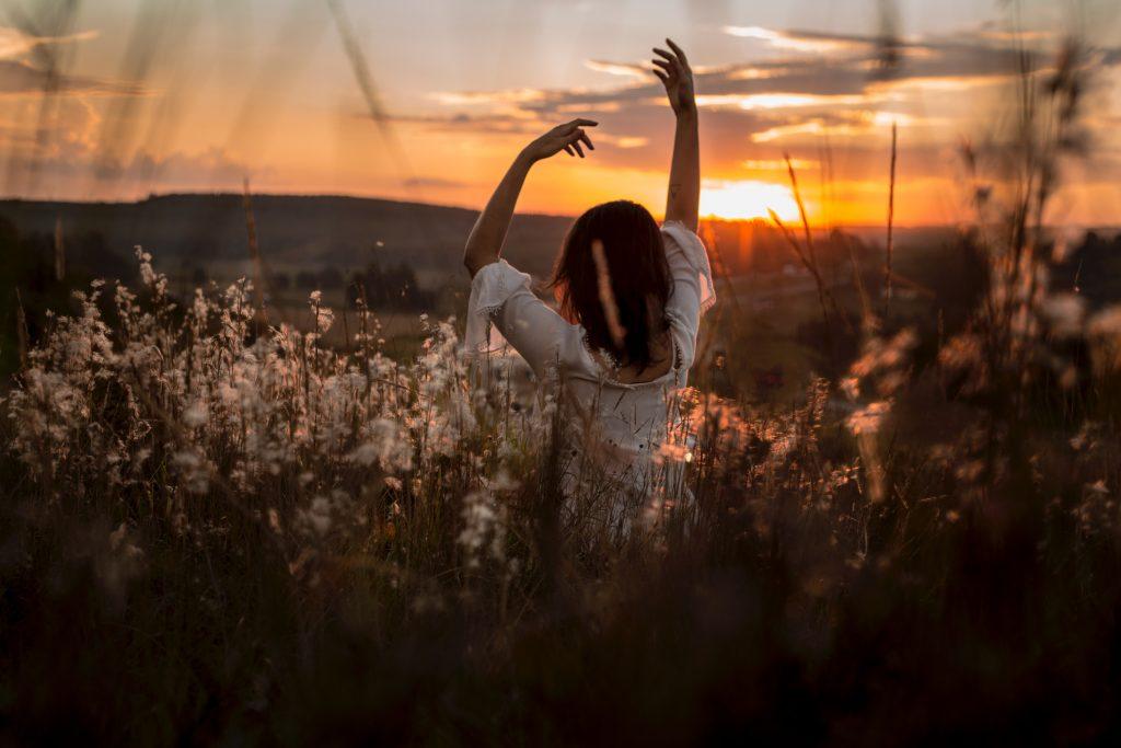 fille qui danse dans un champ de fleurs au coucher du soleil