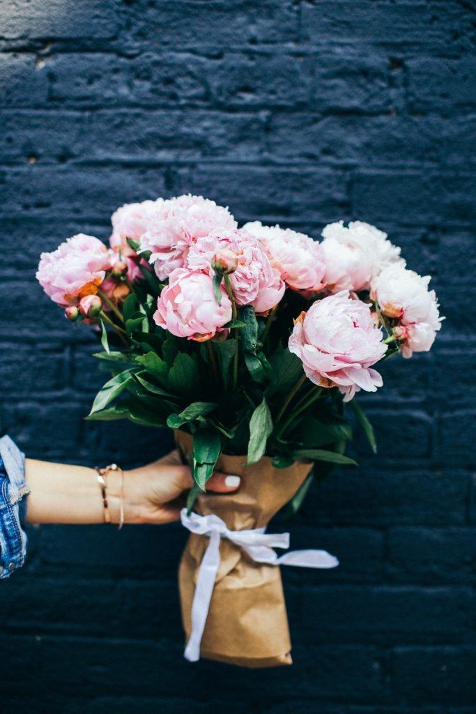 fleurs roses main mur briques