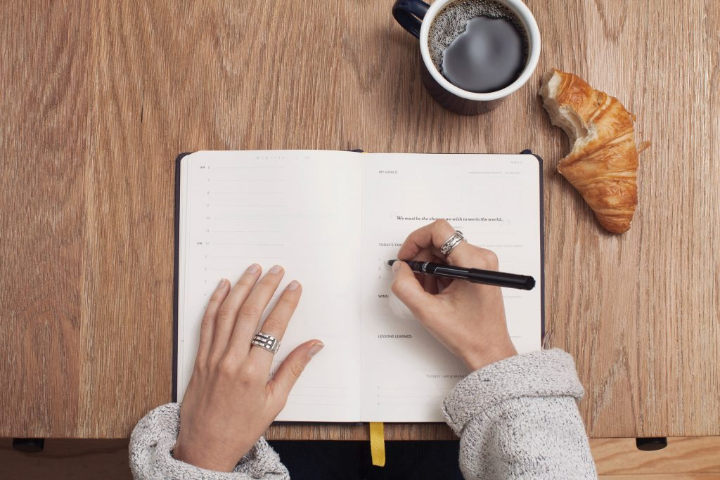 femme qui écrit dans son agenda croissant et café