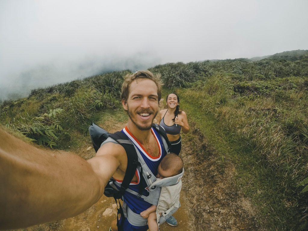 parents avec leur bébé en train de monter une montagne