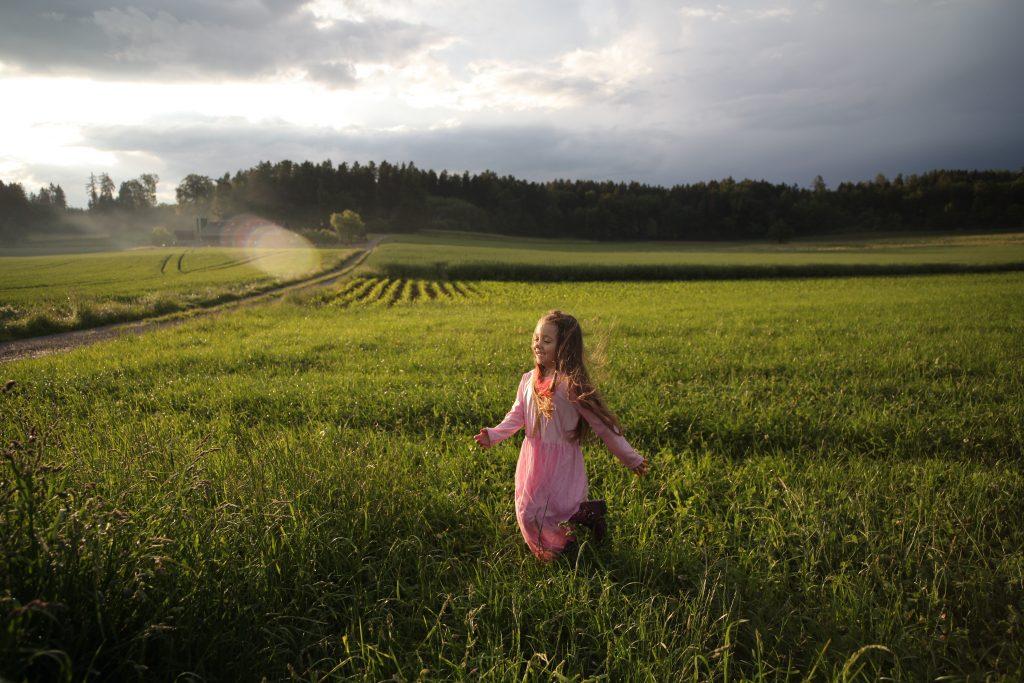jeune fille qui court dans un champ avec une robe rose