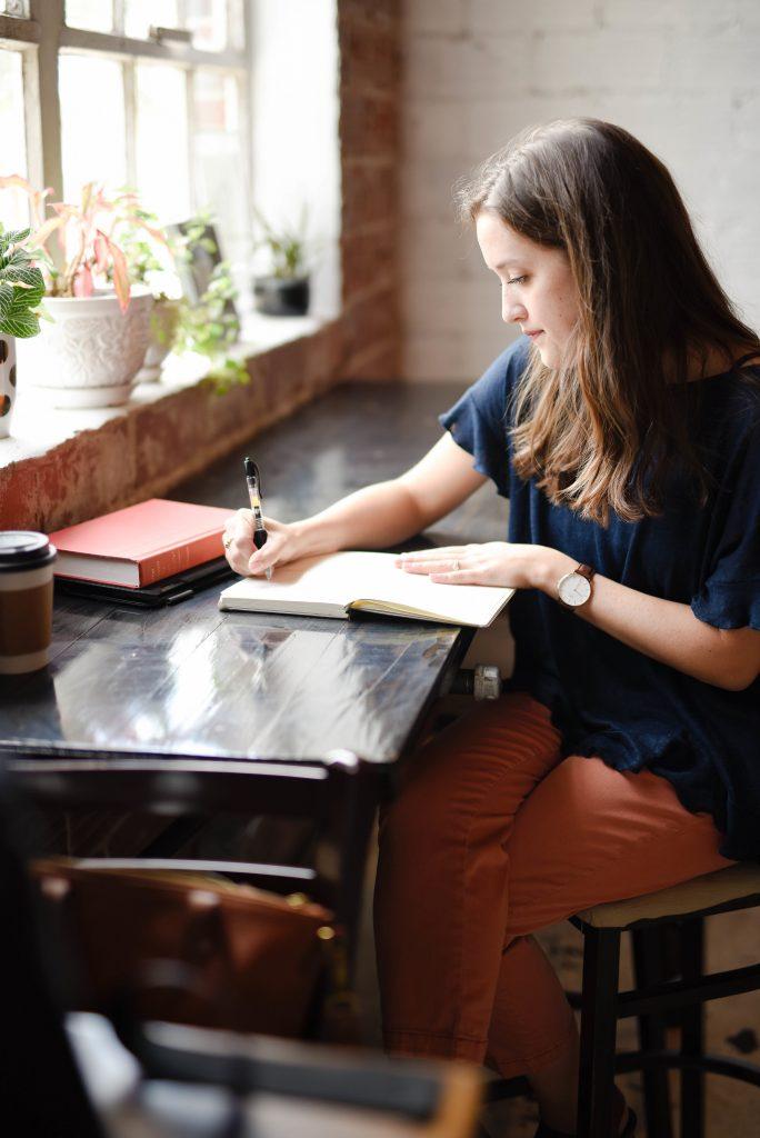 jeune femme qui écrit dans un café