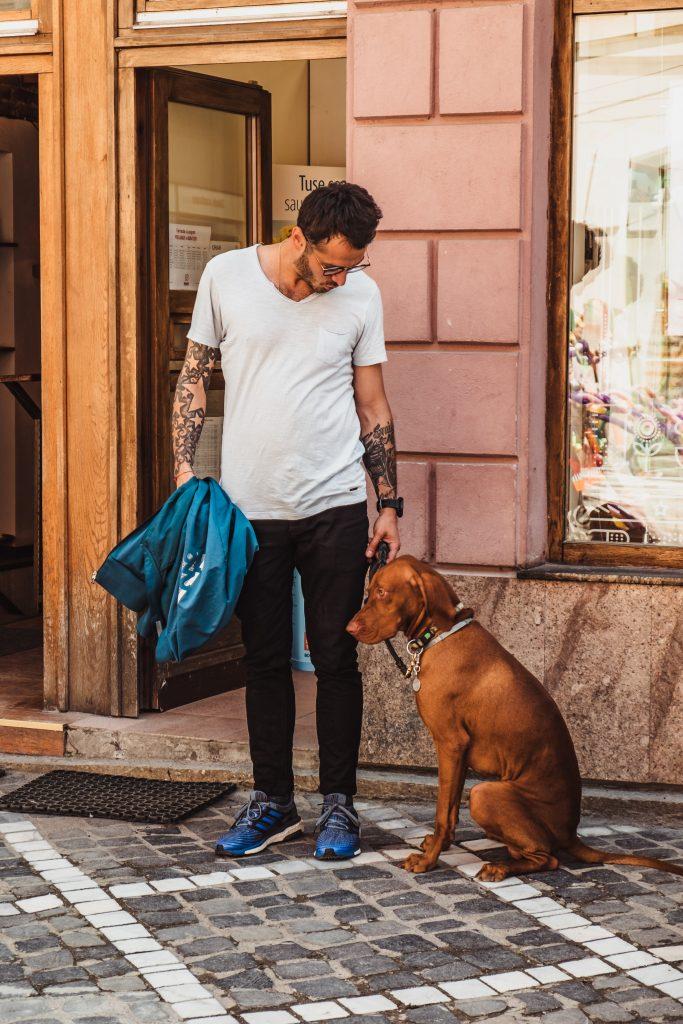 homme qui tient son chien en laisse