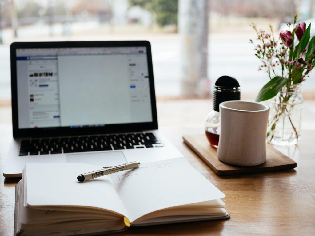 ordinateur ouvert avec cahier, crayon, tasse, fleurs