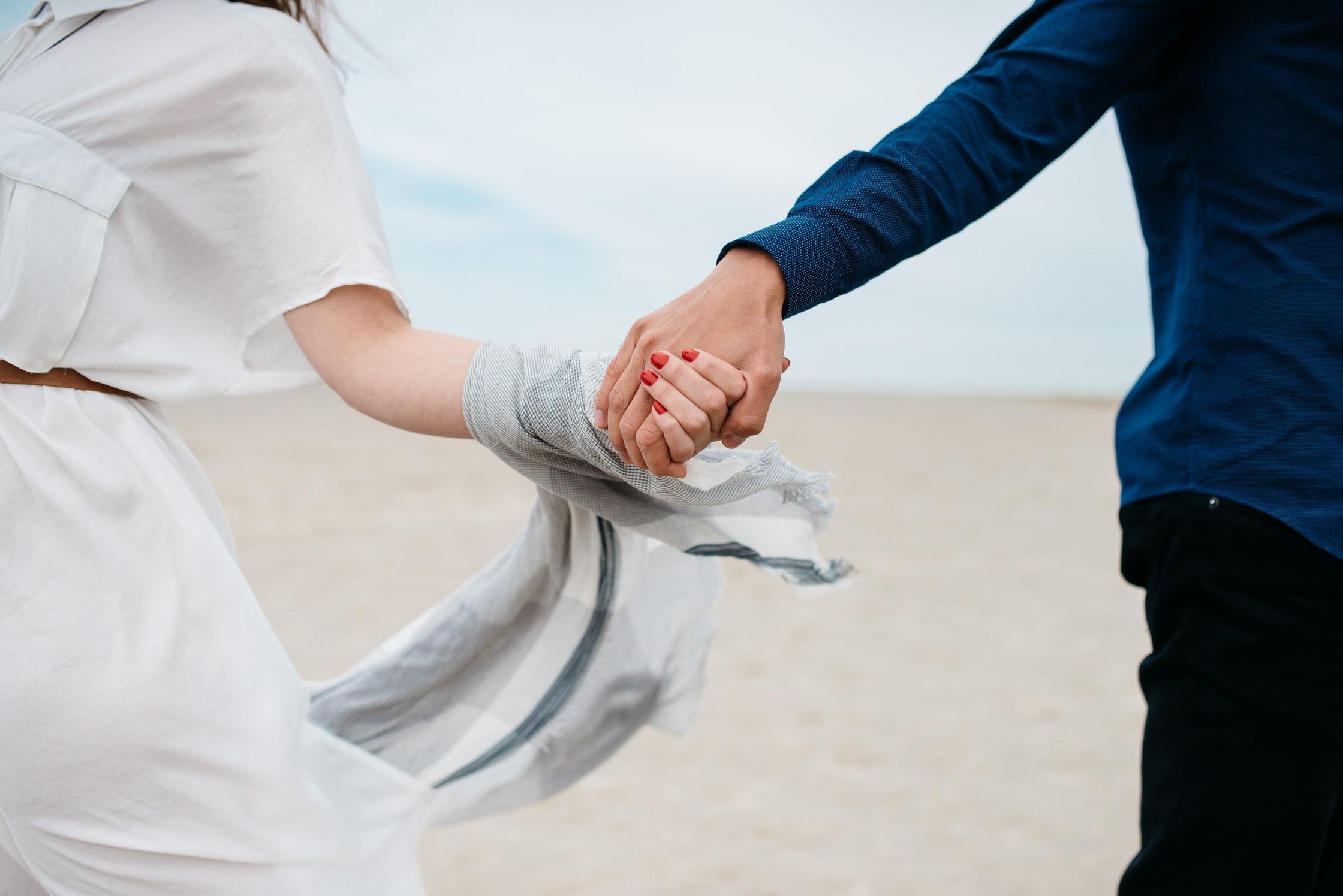 deux personnes qui se tiennent la main dans le vent