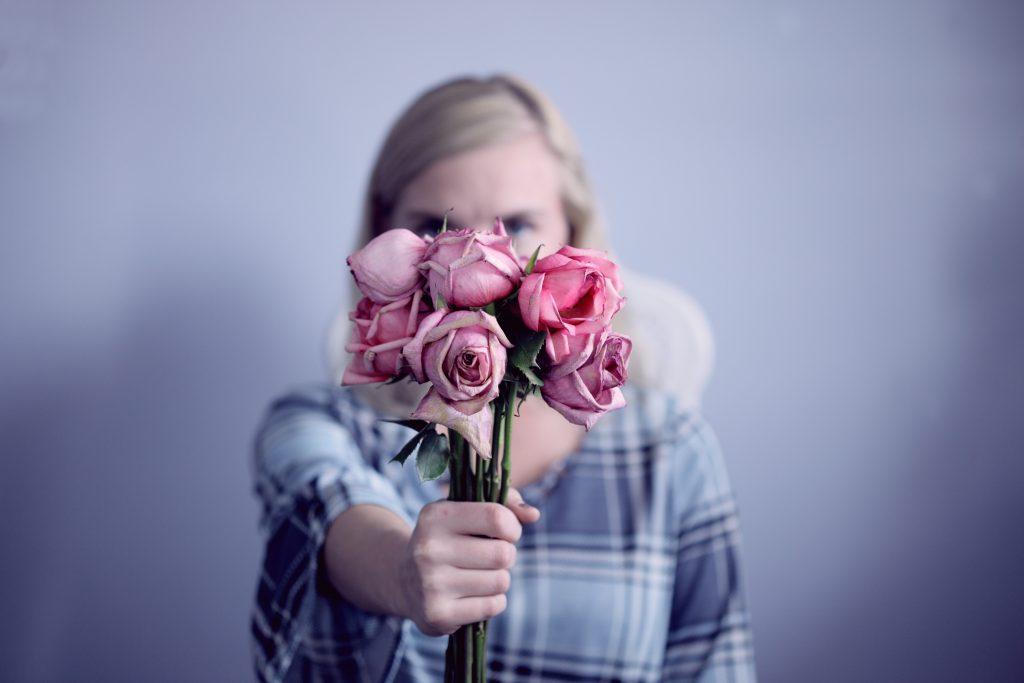 femme qui tend un bouquet de roses