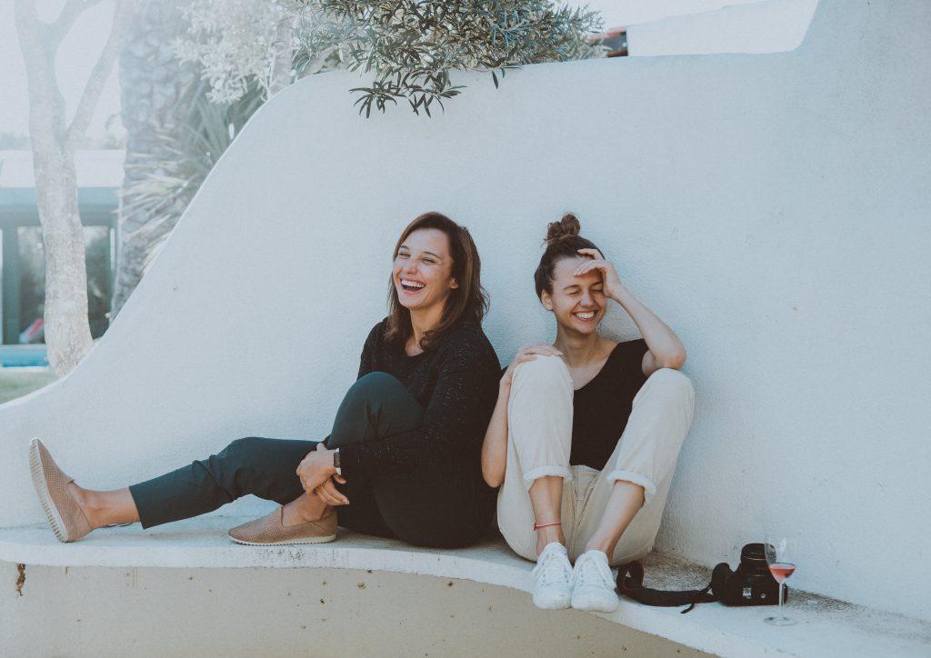 deux femmes qui rient assises contre un mur