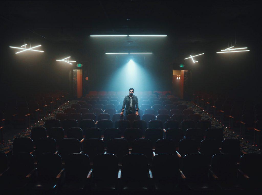 homme seul salle de théâtre projecteur