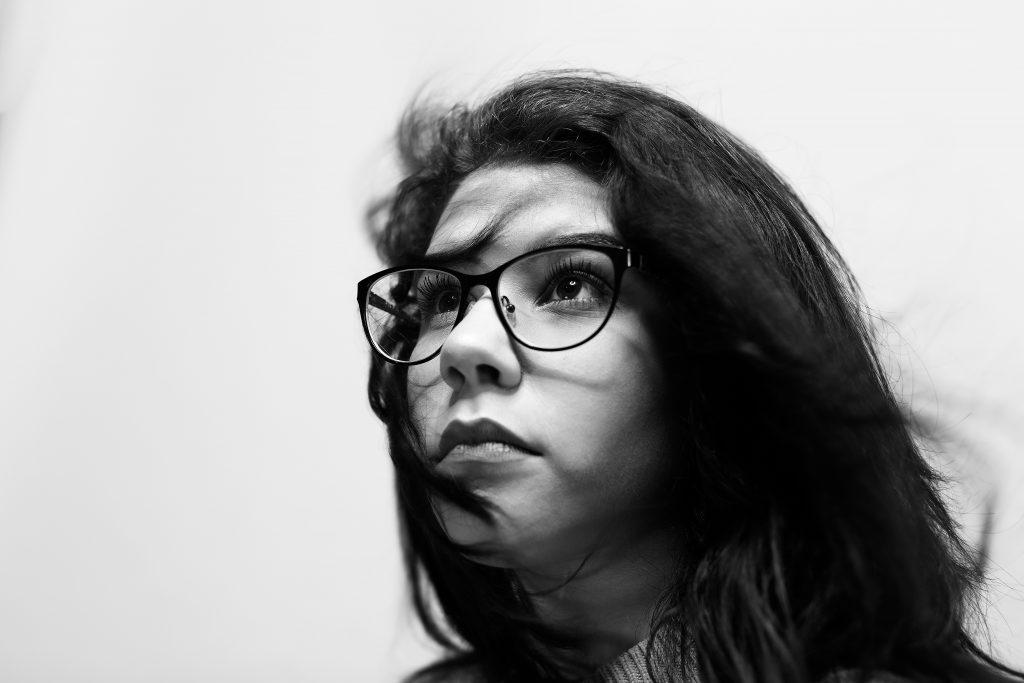 femme qui regarde au loin avec lunettes et cheveux dans le vent