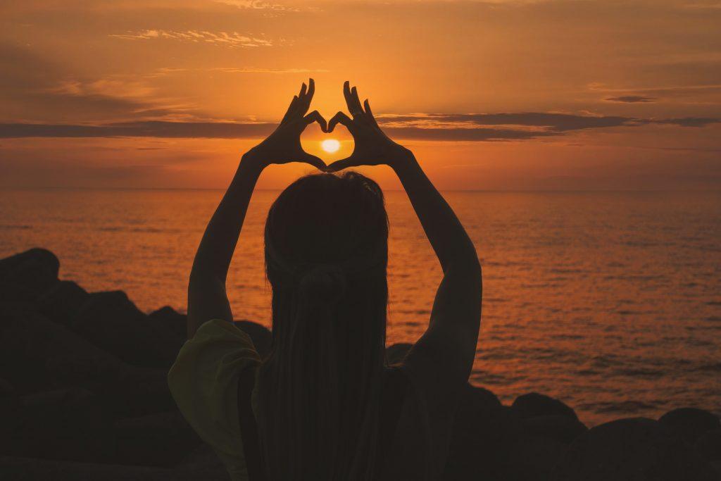 femme qui fait un coeur avec se mains coucher de soleil