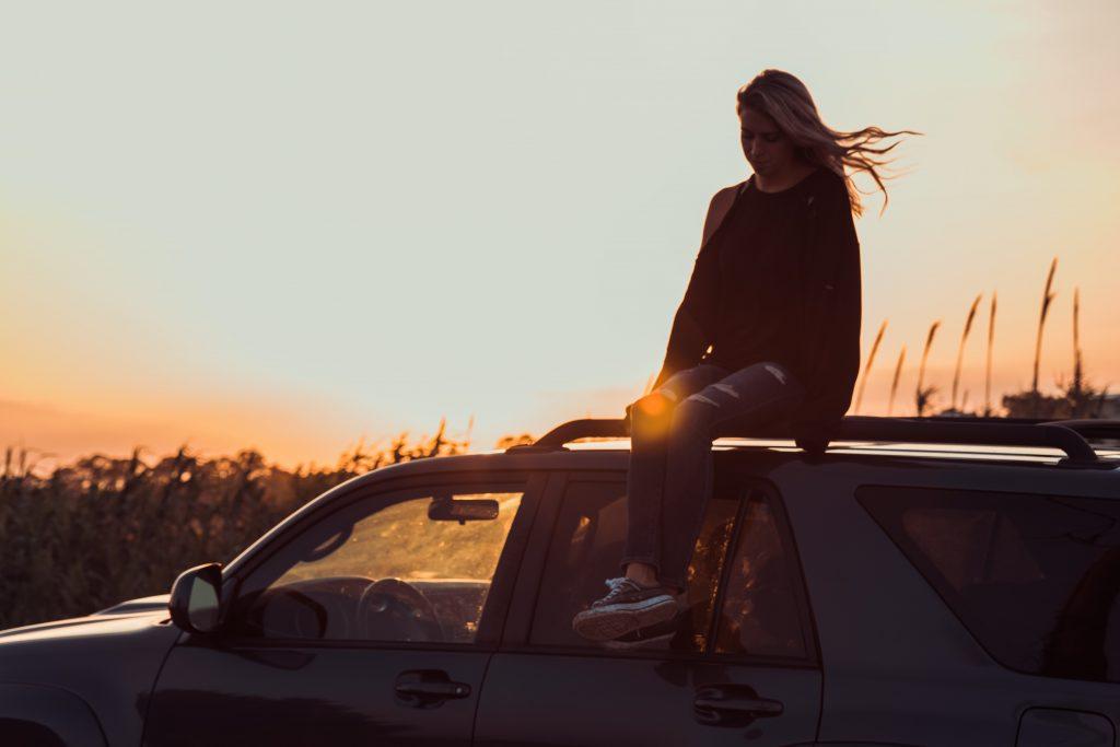 fille cheveux dans le vent assise sur toit voiture