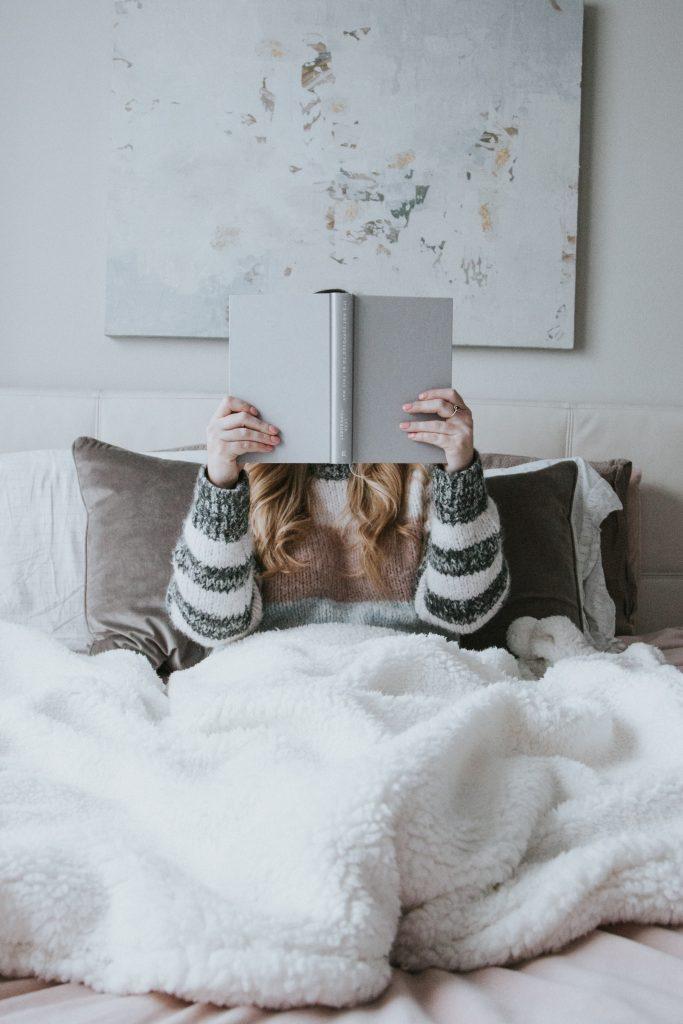 fille qui lit avec roman devant le visage