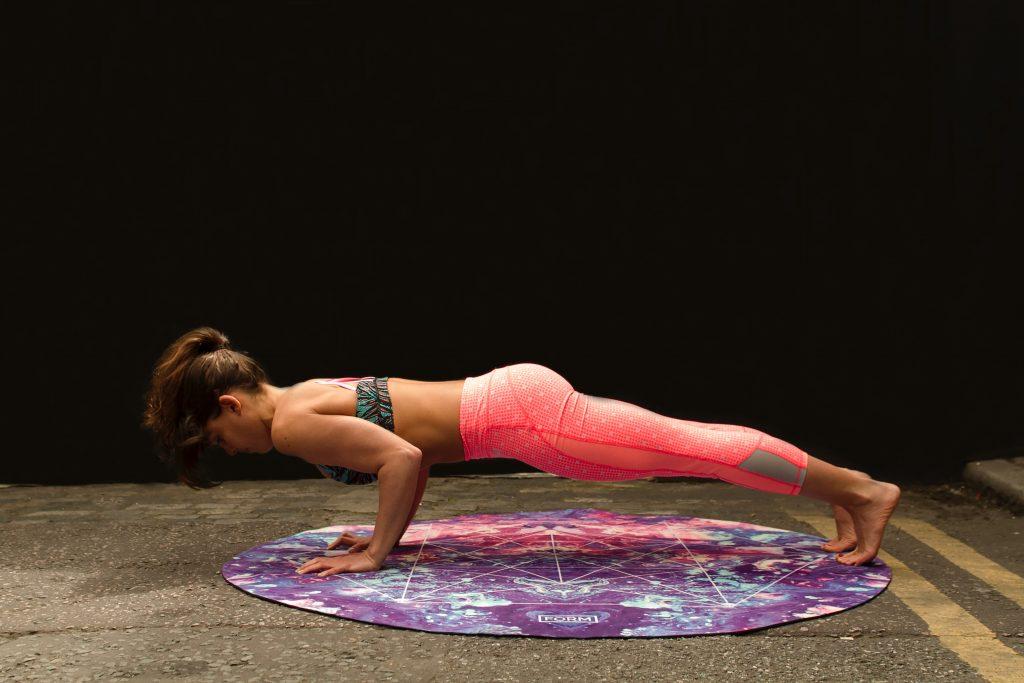 femme qui fait des pompes sur tapis leggings roses