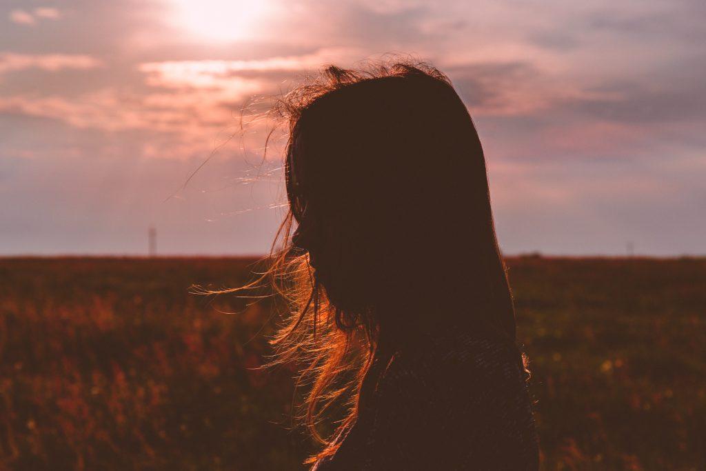 femme de profil cheveux dans le vent coucher de soleil