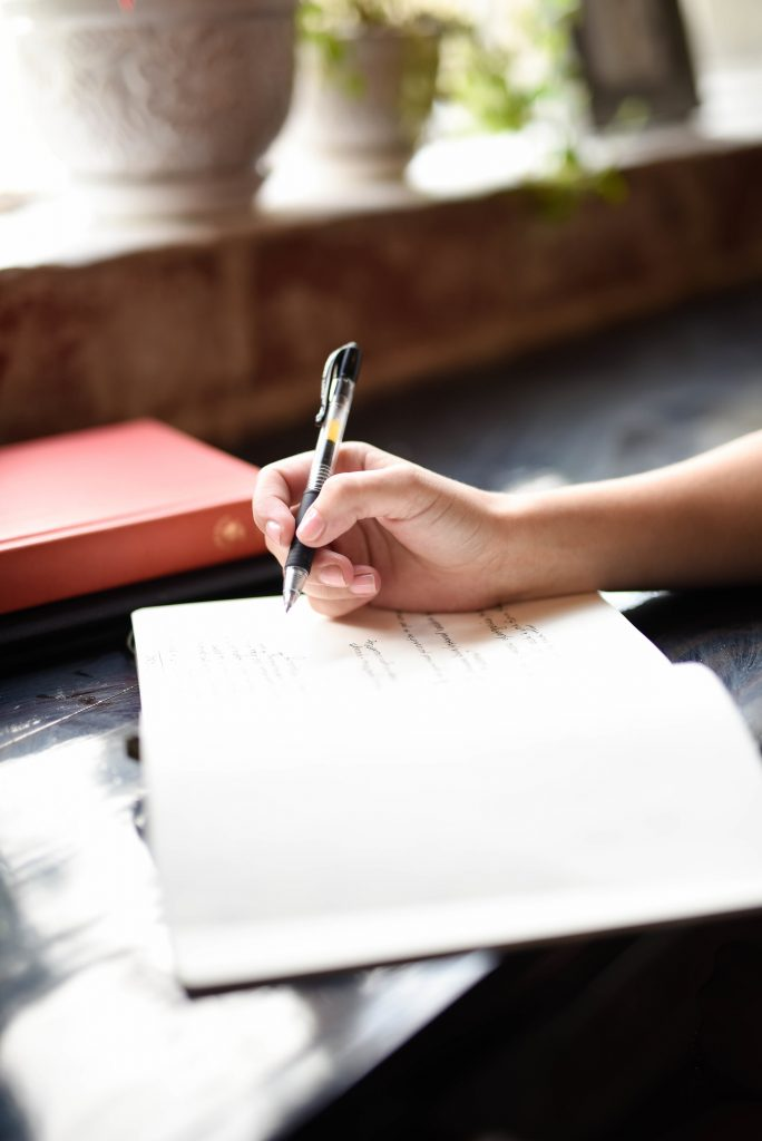 main qui écrit avec stylo dans carnet