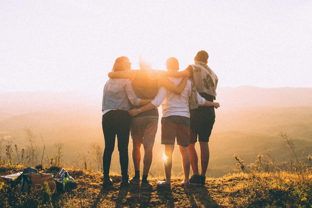 quatre personnes qui tiennent devant coucher de soleil