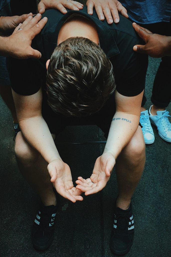 homme tête baissée avec mains sur les épaules