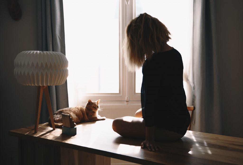 femme assise sur une table avec chat