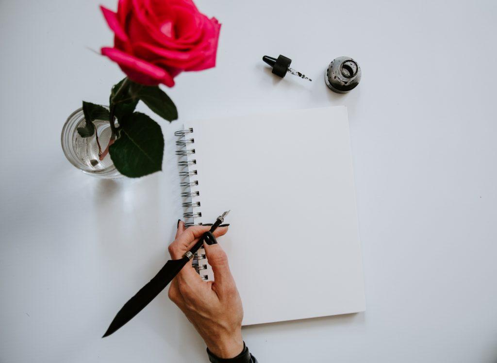 main avec plume papier et rose