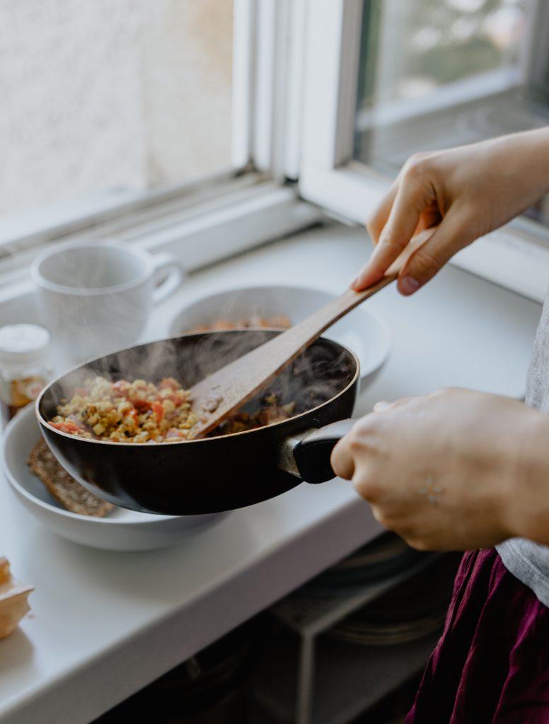 personne qui cuisine dans une poêle