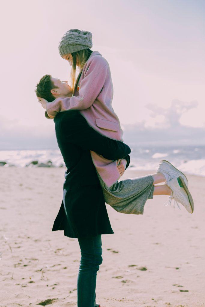 homme qui soulève une femme heureux