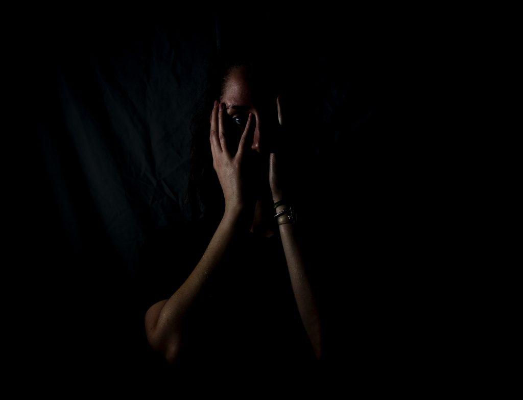 femme dans le noir avec mains dans le visage