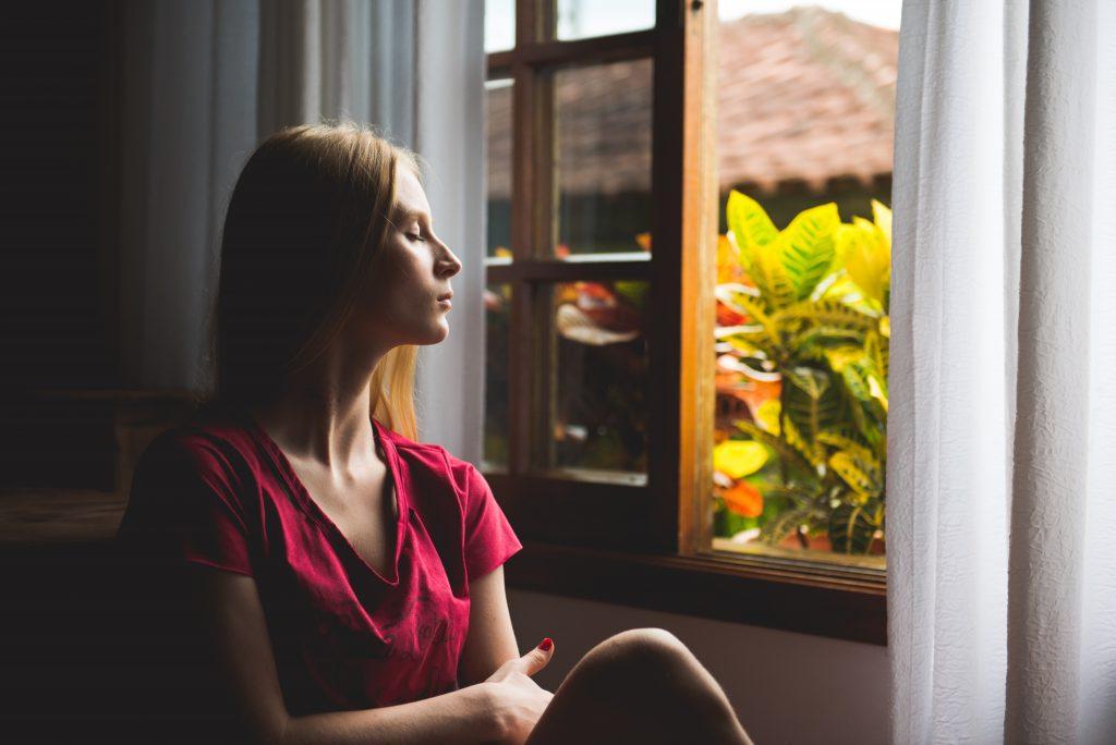 femme qui repsire l'air extérieur fenêtre ouverte