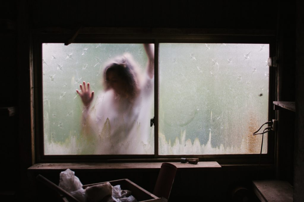 femme derrière une fenêtre embuée