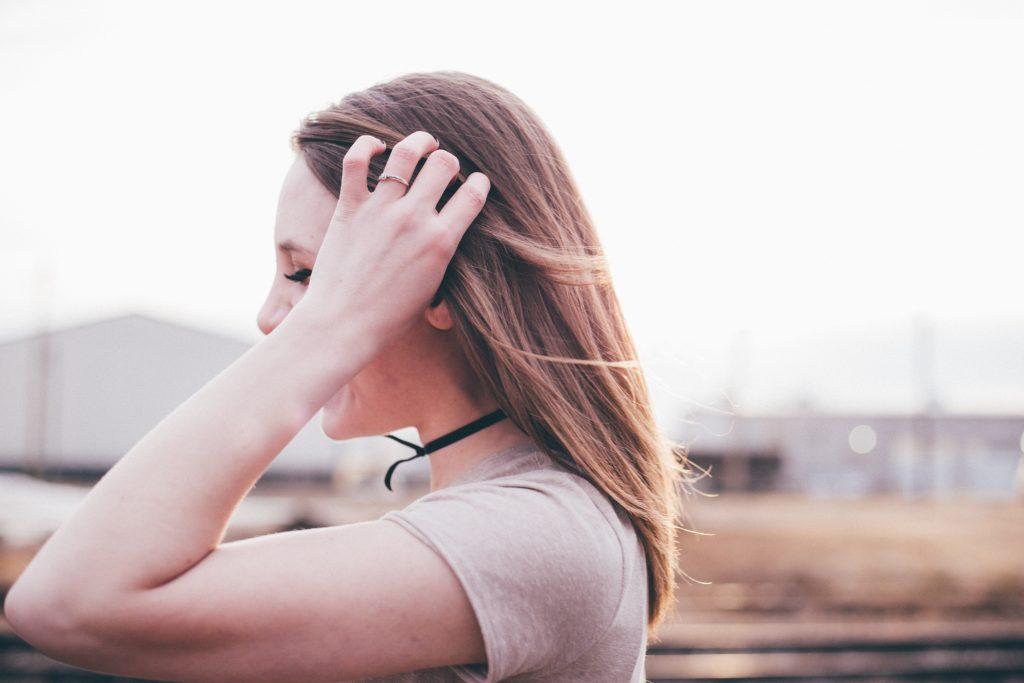 Femme de profil main dans les cheveux