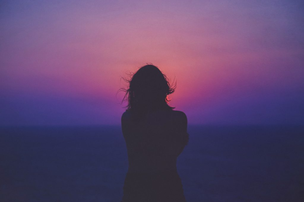 silhouette d'une femme les cheveux dans le vent devant ciel mauve