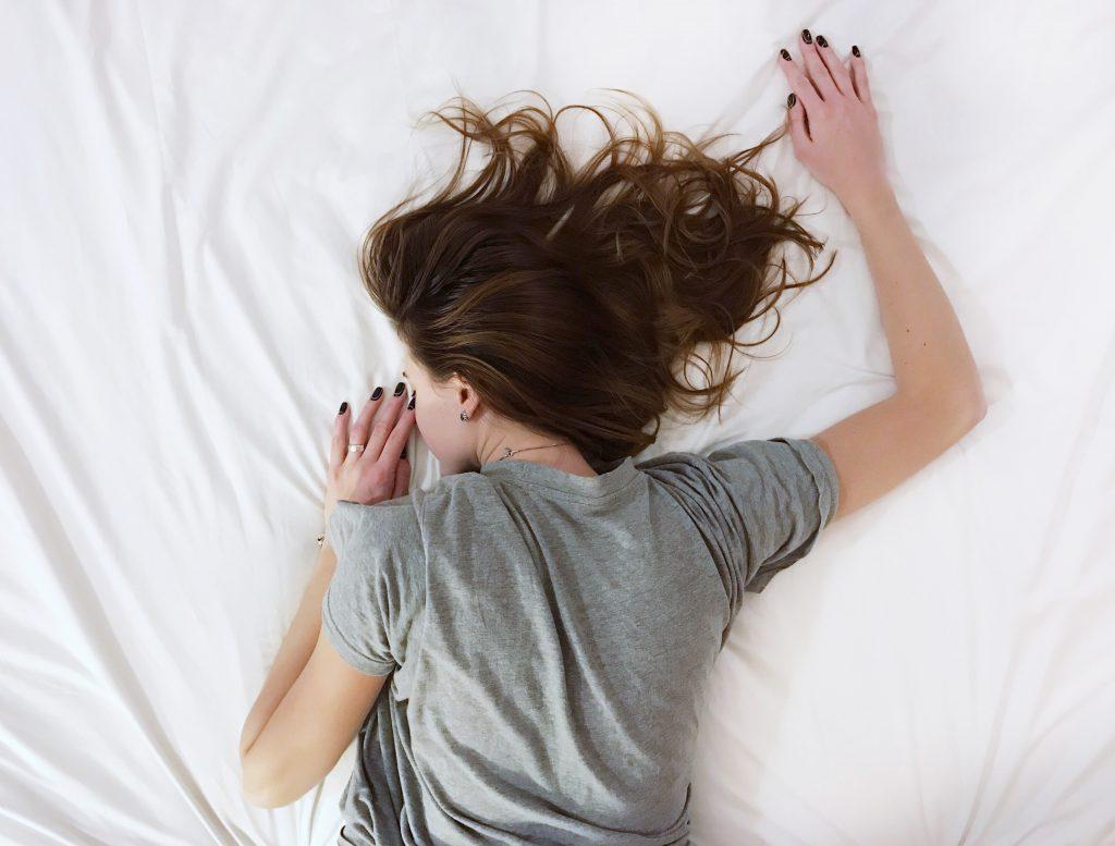 femme couchée sur le ventre lit cheveux éparpillés