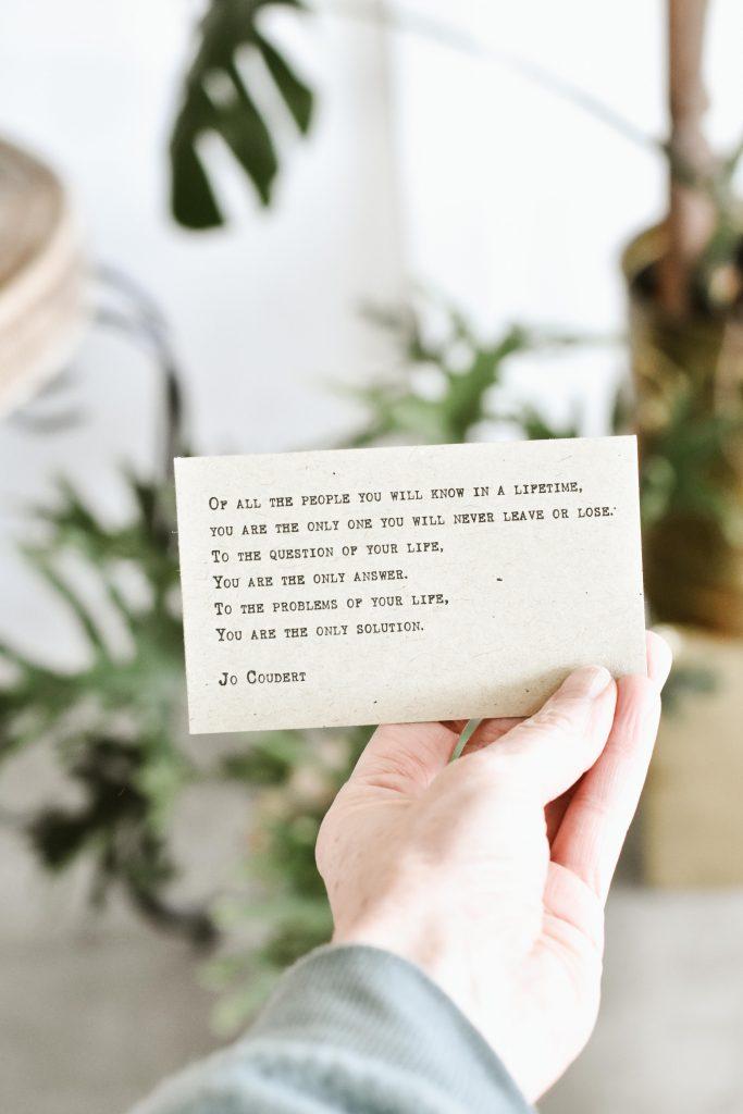 main qui tient petit carton blanc message